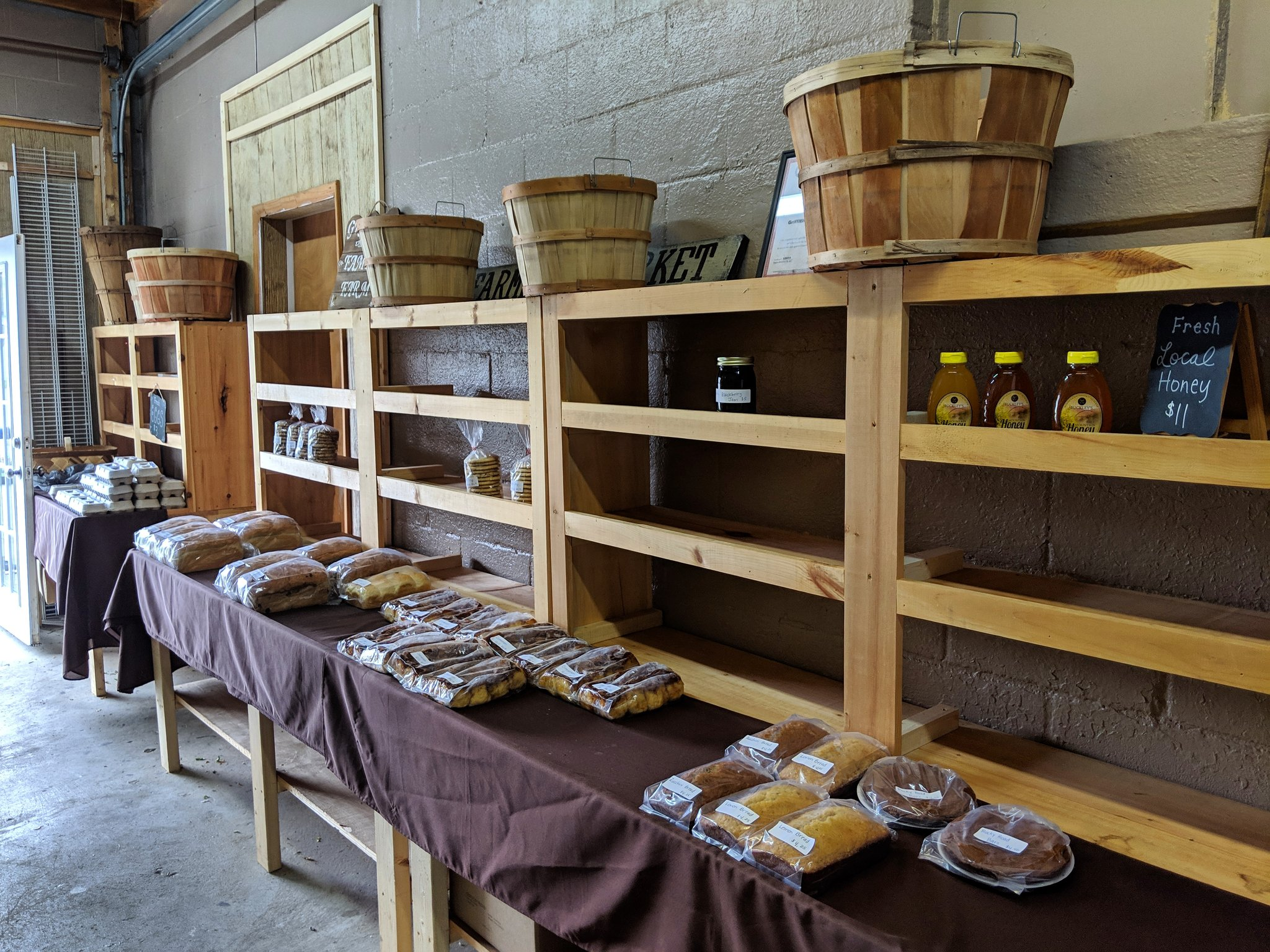 The Griffith Family Farm stall featuring tables and shelves with local honey, baked goods like bread and cinnamon rolls, and cartons of one dozen eggs.