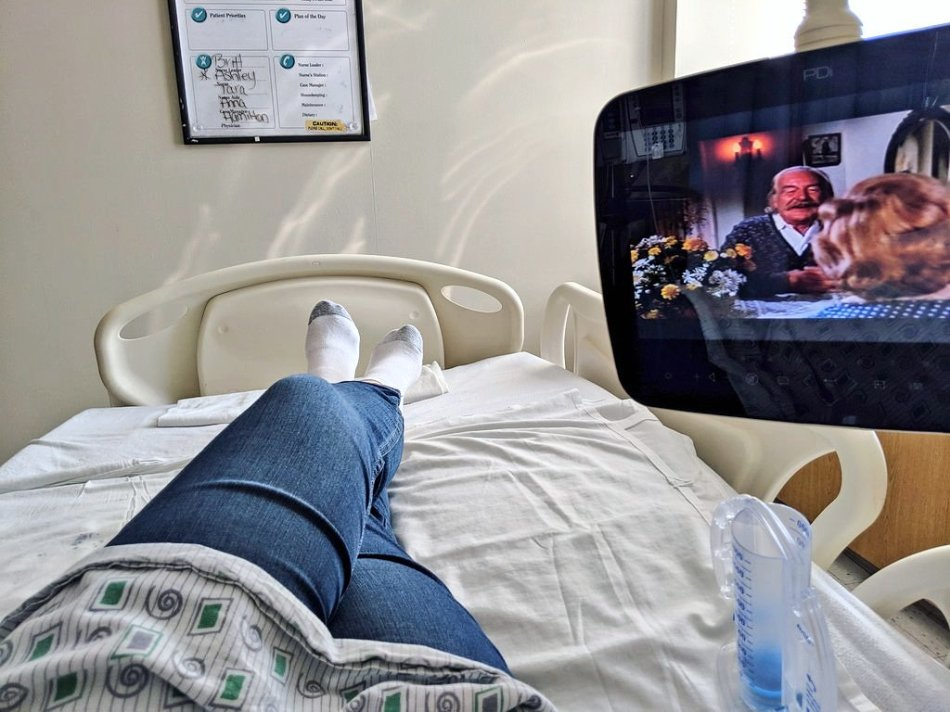 A point of view shot of a woman's crossed legs as she lies on a hospital bed and watches television. The television show The Waltons is playing.