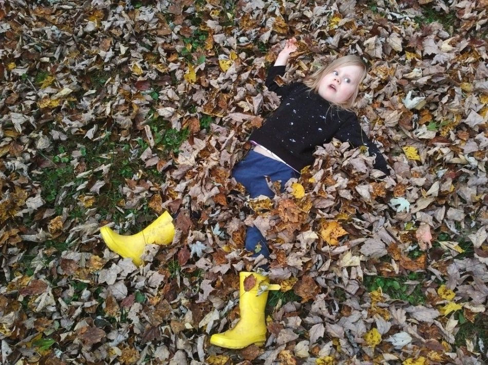 Young girl making a silly expression as she lies down in a pile of leaves - You Will BEE Fine blog