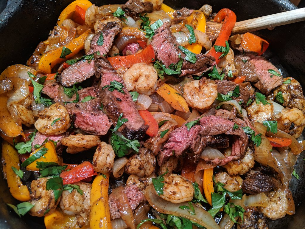 A skillet mix of sirloin steak slices and sauteed peppers, onions, and shrimp, as well as fresh cilantro.